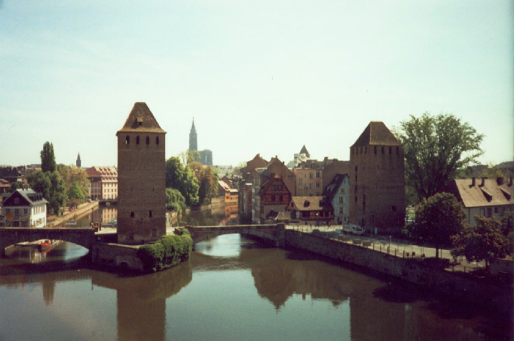 Watchtowers stand vigil over canal in Strasbourg while cathedral stands vigil over the town, photograph by C. W. Booth